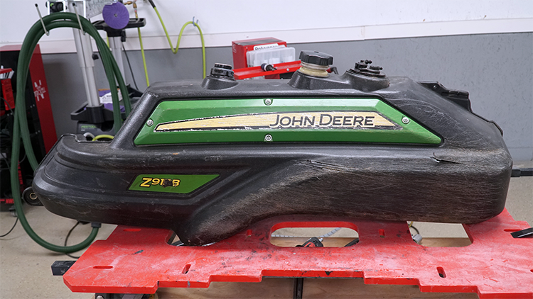 A black gas tank for a John Deere zero turn mower.