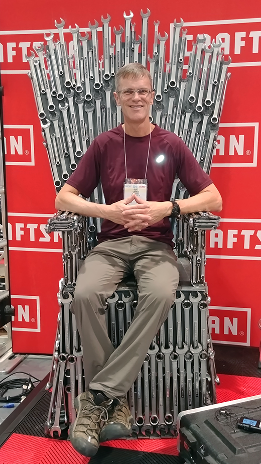 Kurt sitting on a throne made of wrenches