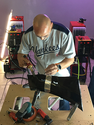 A man using a nitrogen plastic welder to repair part of a bumper.