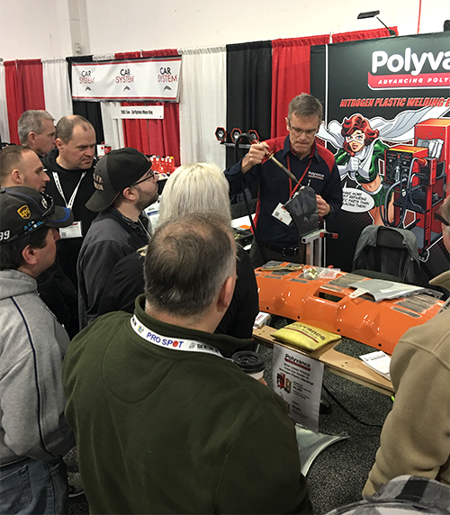 Kurt welding a bumper with the nitrogen plastic welder in front of a crowd