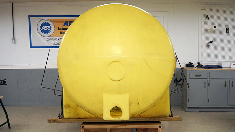A giant yellow agricultural tank. There is a large hole cut out on the front side.