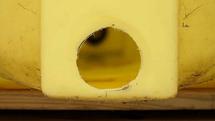 Close up of the hole on the front side of a giant yellow agricultural tank.