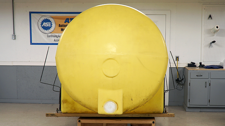 A giant yellow agricultural tank. There is no longer a hole. The plug that was used to fill the hole is made from a white sheet of polyethylene.