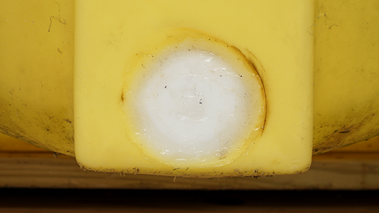 Close up of the repaired area on the front side of a giant yellow agricultural tank. There is no longer a hole. The plug that was used to fill the hole is made from a white sheet of polyethylene.