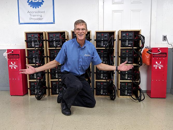 Kurt in front of a stack of 20 6085 Nitro Fuzer nitrogen plastic welders and two 6066 Nitrocell nitrogen generators.
