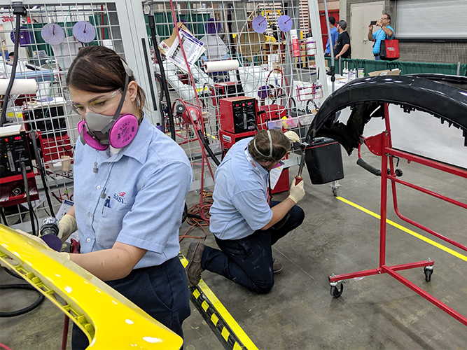 Two competitors using various tools to repair plastic bumpers.
