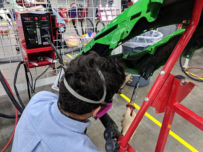 A competitor using a nitrogen plastic welder to weld a plastic bumper.