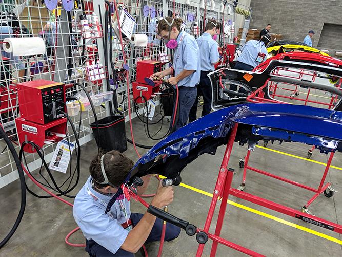 Several competitors using various tools to repair plastic bumpers.