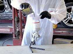 A man filtering Bumper and Cladding Coat Adhesion Primer into his spray gun.