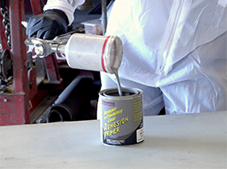 A man pouring paint out of a paint gun and into a can.