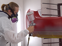 A man spraying a topcoat on a bumper.