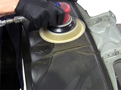 Using 80 grit sandpaper in a dual-action sander to feather back the repair area.