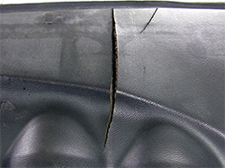 A large split in the vinyl of a Datsun 280Z dashboard.